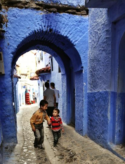 The brothers walking through a blue passage in Chefchaouen